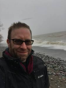 Author stands next to high waves and misty Lake Ontario