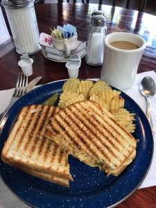 Spicy chicken panini with coffee on a diner table
