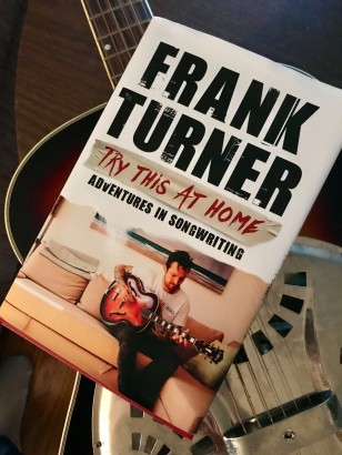 "Photo of Frank Turner's ""Try This At Home"" songwriting book atop a dobro guitar"