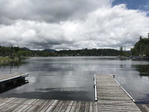A view into a clear Saranac Lake from a parkside pier