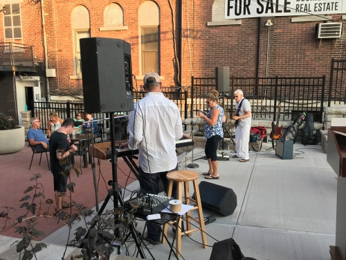 A quartet plays rock music for a crowd in Water Street Square