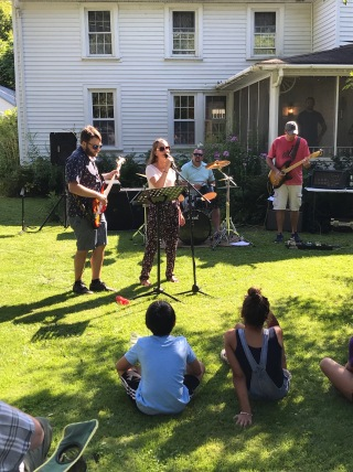 The band Be Kind, Rewind performs '90s rock on a front lawn