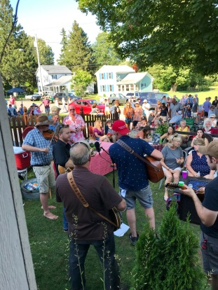 The New Snip City bluegrass band plays in a yard surrounded by music fans