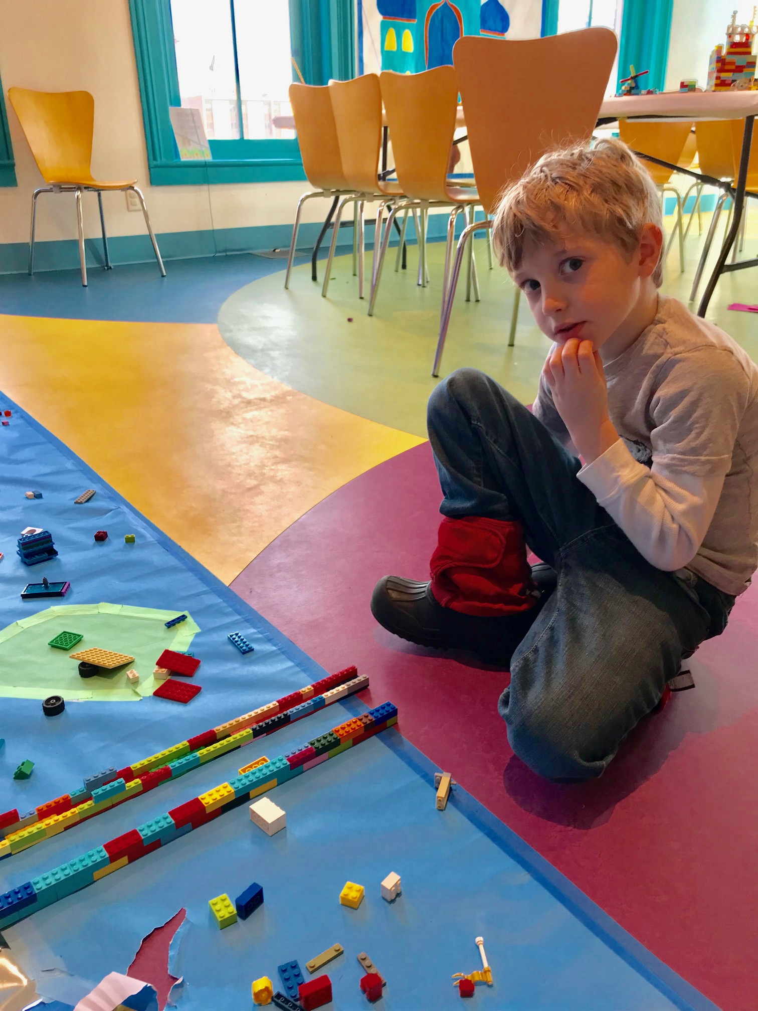 A young boy playing with Legos at a children museum