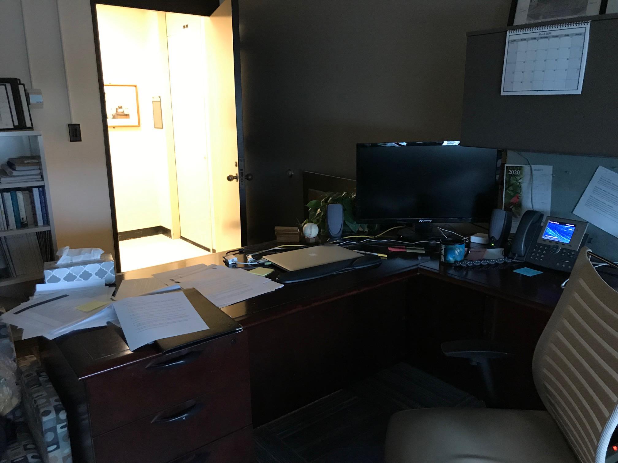 A darkened office with an open door